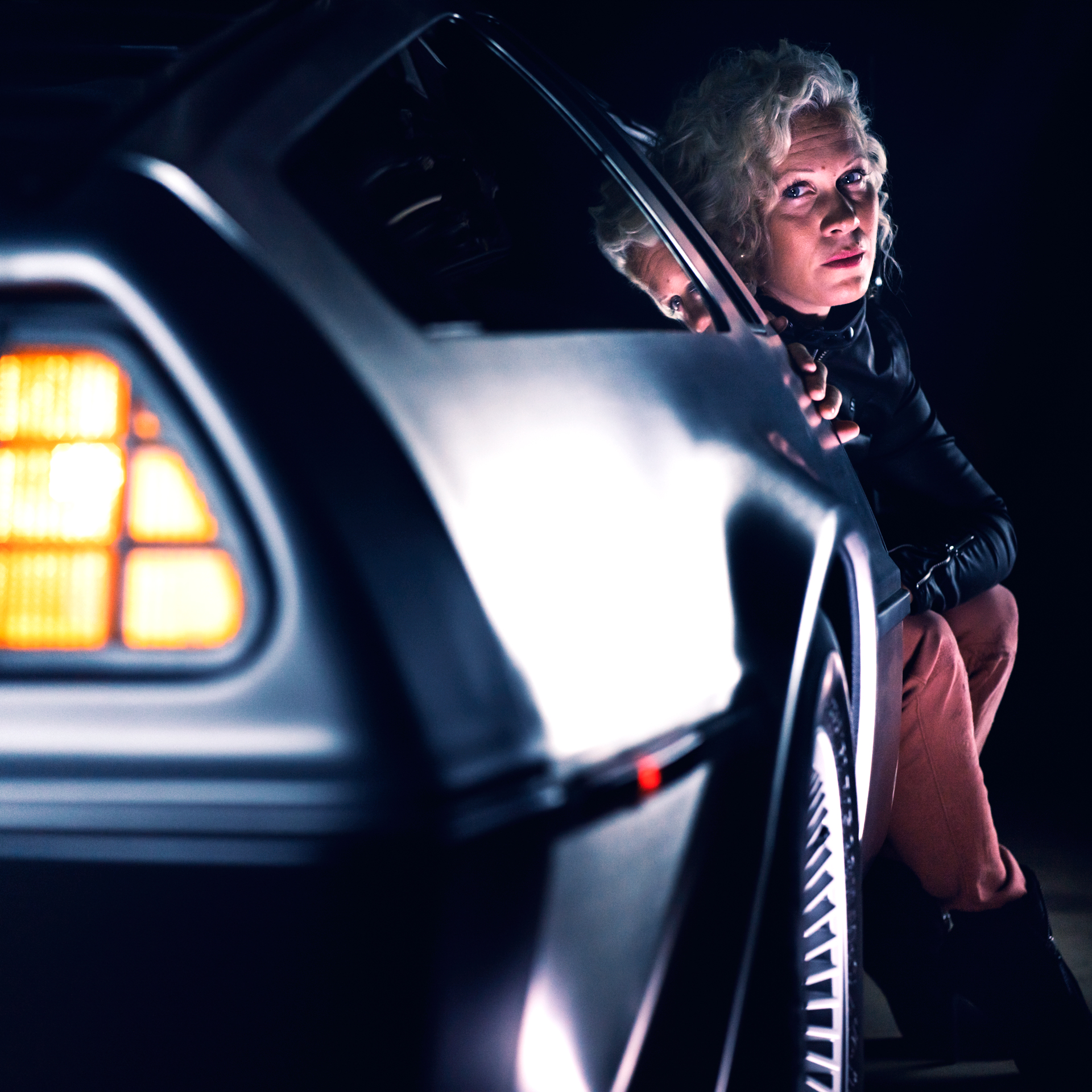Anna Sköld sitting in a DeLorean